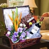 A Bottle of Red Wine with Chocolates and Flower Arrangement in a basket.